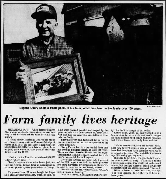 Eugene Obery and Obery Farms - Eugene Obery holds a 1930s photo of his farm,...