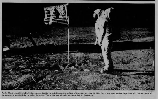 Buzz Aldrin beside American flag on surface of moon -